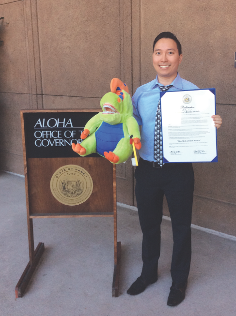 Dr. Morita poses with Fred the Floss-a-saurus and displays a signed proclamation declaring February Give Kids  A Smile Month in Hawaii.