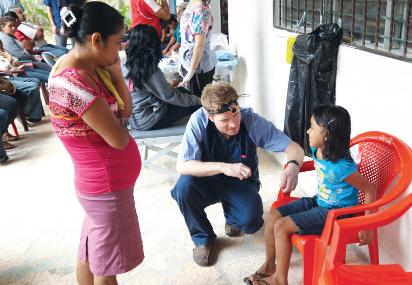 Volunteer: Dr. Charlie Clark, left, treats a patient during his 2013 visit to Guatemala.