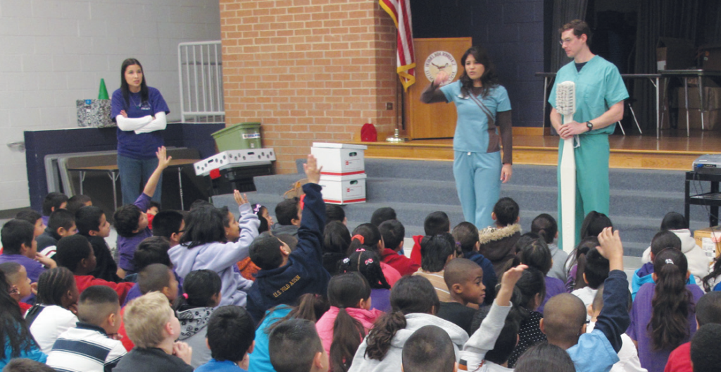 Giving back: Drs. Ensy Atarod and Jeff Dykes give an oral health presentation to Austin students as part of Dr. Atarod's leadership project.