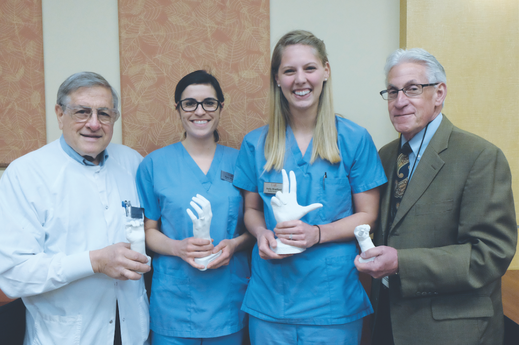 Cast of fundraisers: A selection of the AO Handmakers' work is on display with, from right, Dr. Lawrence Gettleman, University of Louisville lecturer and advisor to Alpha Omega; Sara Nelson, Alpha Omega member and third-year dental student; Holly Bradford, Alpha Omega president and third-year dental student; and Dr. Lee Mayer, Alpha Omega faculty co-advisor.