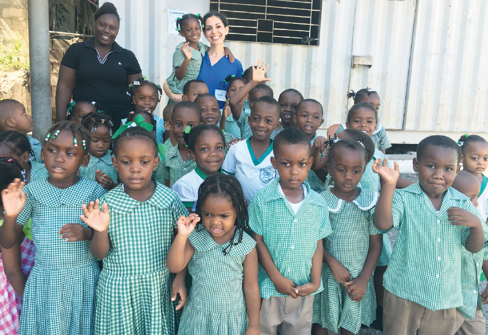 Busload: Dr. Nayrika Salamati poses for a photo with about two dozen children and their teacher during an international volunteer trip held May 2016 in Hanover Parish, Jamaica. The children had just gotten out of their school bus and lined up to sing before they were seated to receive oral hygiene instructions and to be seen by a dentist.